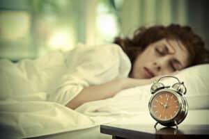 Kvinde ligger og sover med vækkeur